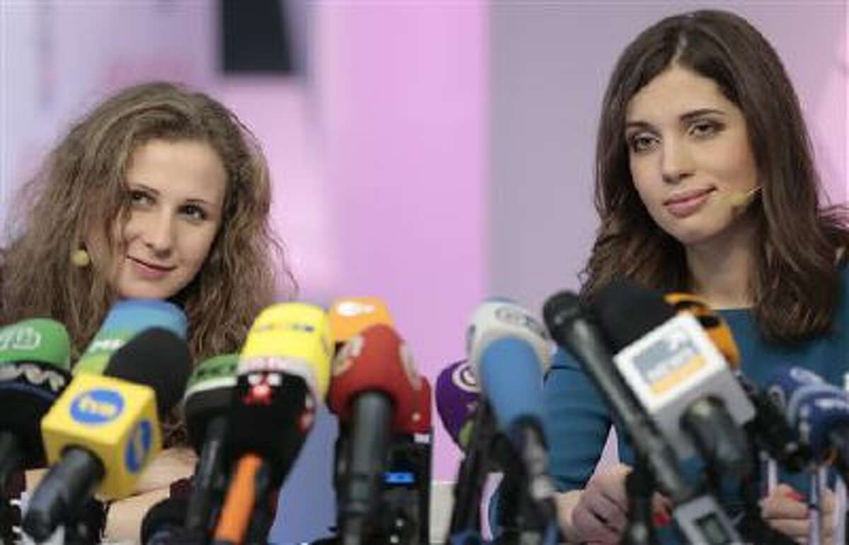 Russian punk band Pussy Riot members Nadezhda Tolokonnikova, right, and Maria Alekhina smile during their news conference in Moscow, Russia, on Friday, Dec. 27, 2013. Tolokonnikova and Alekhina were granted amnesty on Monday, Dec. 23, two months short of their scheduled release after spending nearly two years in prison for their protest at Moscow's main cathedral.