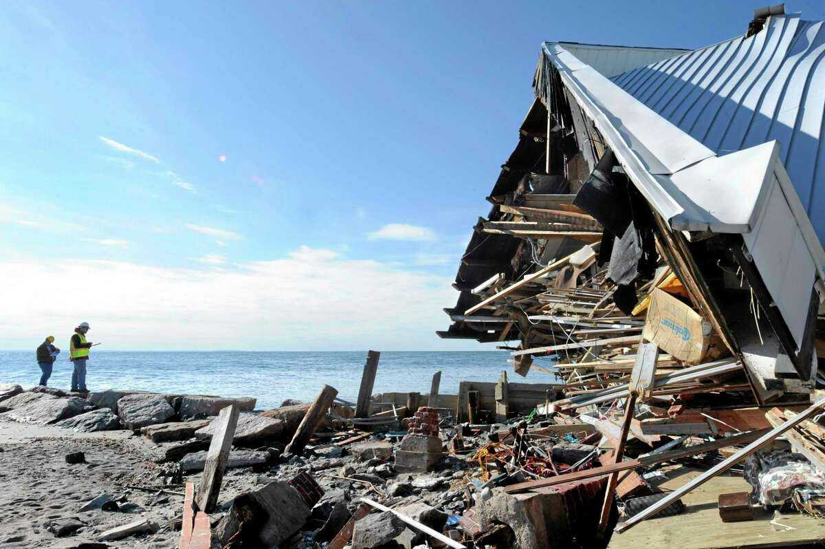In this Wednesday, Nov. 14, 2012 photo, engineers stand next to the destroyed home of Benjamin Barton as they assess damage to homes from Superstorm Sandy along Fairfield Beach Road in Fairfield, Conn. (AP Photo/Jessica Hill)