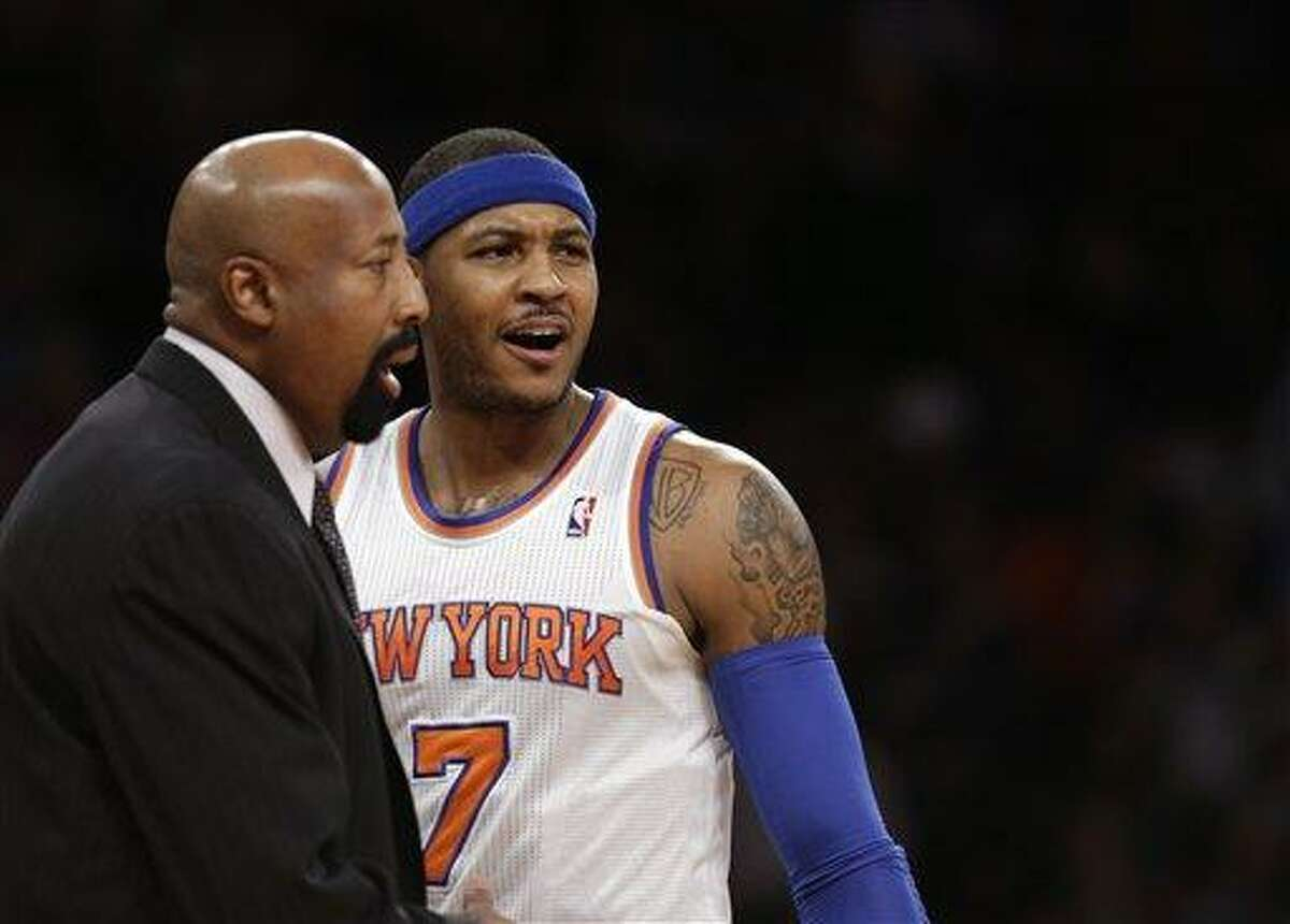 New York Knicks head coach Mike Woodson walks away as New York Knicks forward Carmelo Anthony (7) reacts to a call in the first half of their NBA basketball game against the New Orleans Hornets at Madison Square Garden in New York, Sunday, Jan. 13, 2013. (AP Photo/Kathy Willens)