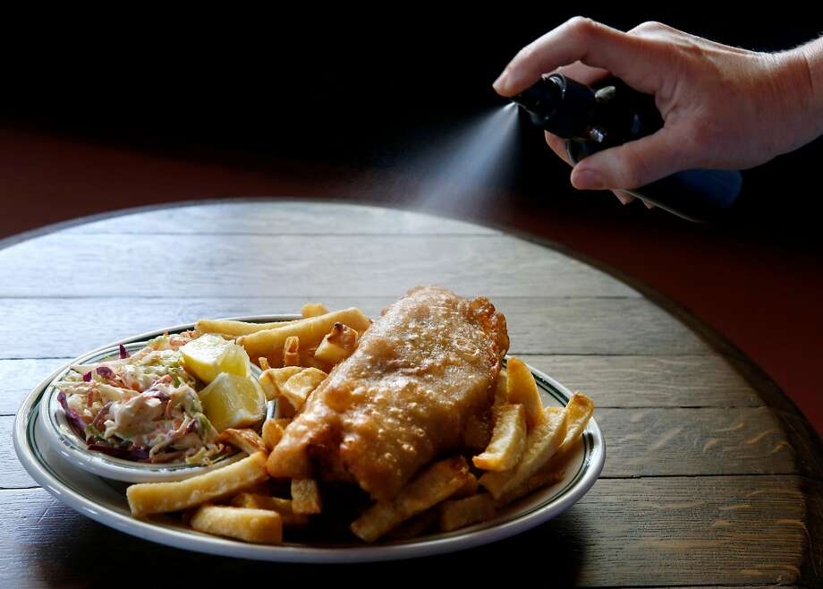 An order of fish and chips is spritzed with malt vinegar from a spray bottle — perhaps not an application used in the old sod, but it prevents the food from getting soggy. Photo: Paul Chinn, The Chronicle