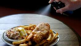 An order of fish and chips is served with malt vinegar in a spray bottle at Sl�inte, a new Irish pub in Oakland, Calif. on Saturday, July 22, 2017.