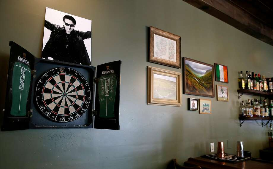 A portrait of Bono hangs above the dartboard at Sláinte. Photo: Paul Chinn, The Chronicle