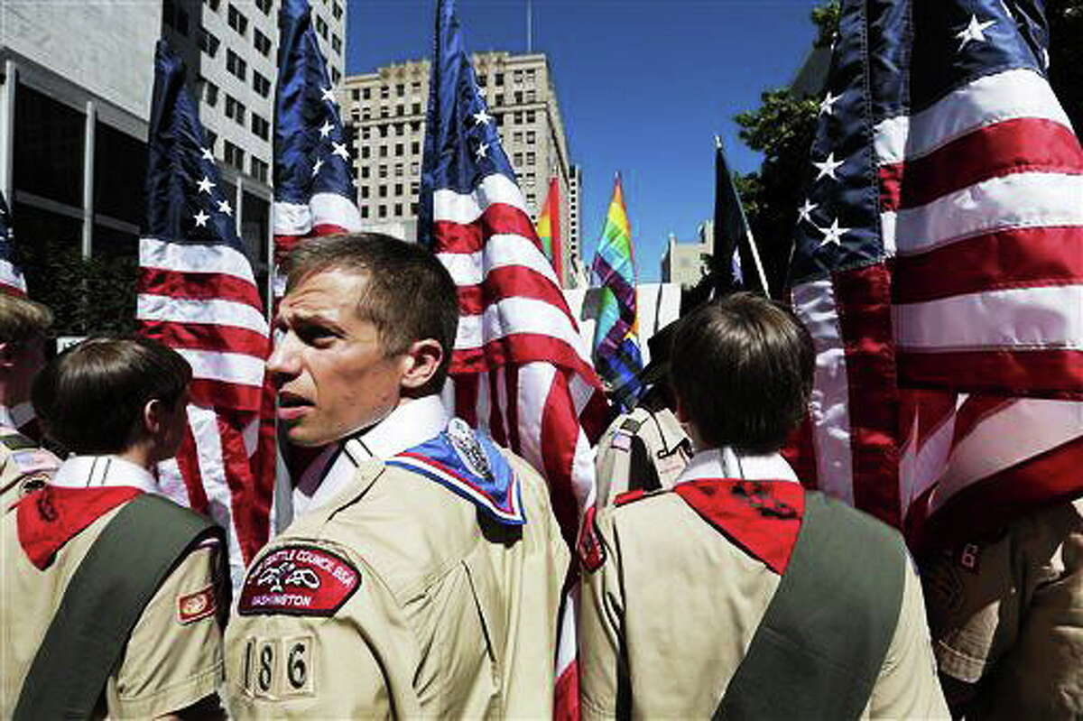 FILE - In this June 30, 2013 file photo, Boy Scouts from the Chief Seattle Council carry U.S. flags as they prepare to march in the Gay Pride Parade in downtown Seattle. The Boy Scouts of America, in the most contentious change of membership policy in a 103-year history, will accept openly gay youths in Scout units starting on New Year's Day 2014. (AP Photo/Elaine Thompson, File)