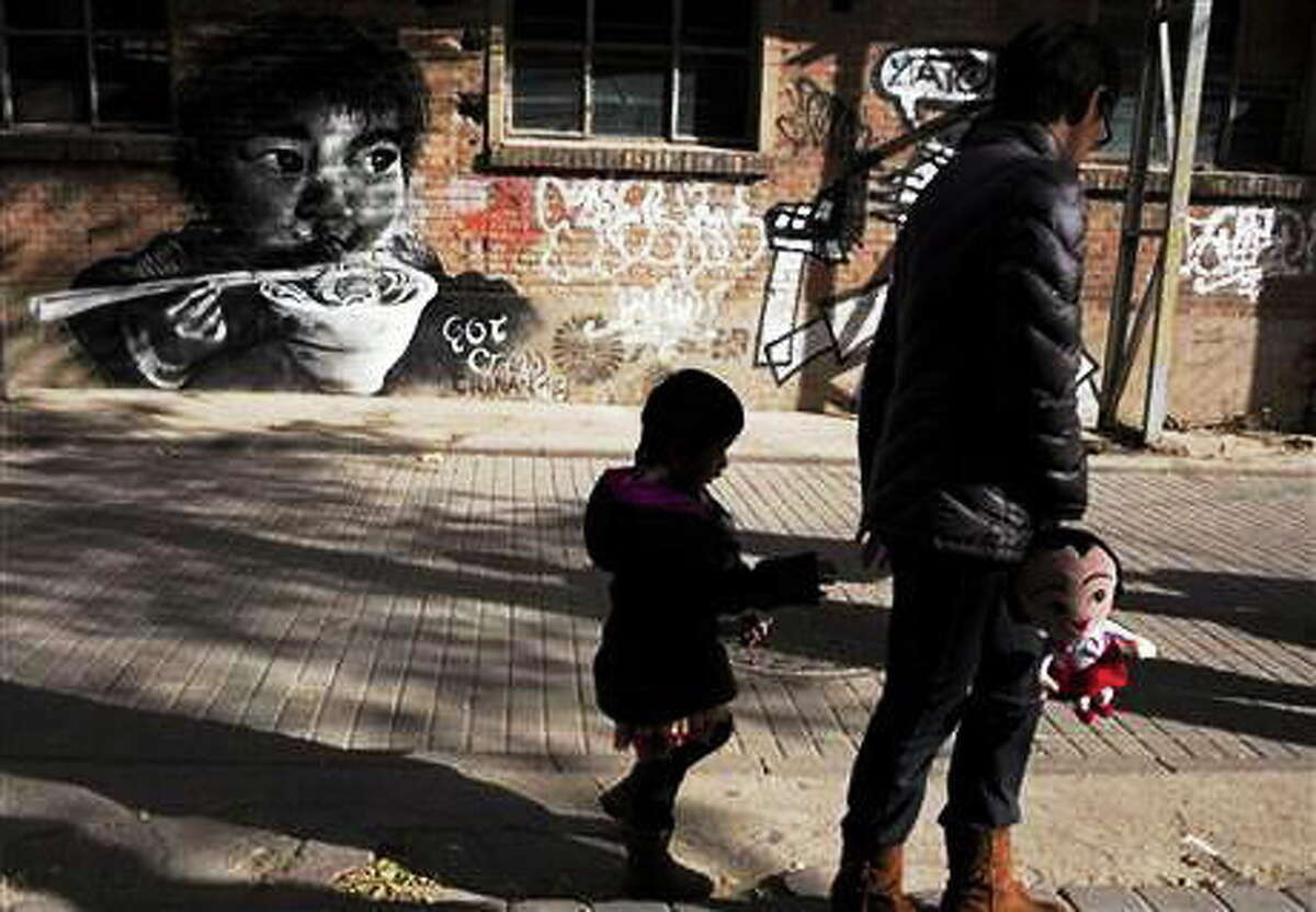 FILE - In this Nov. 17, 2013 file photo, a woman leads a child while holding a doll as they walk near mural depicting a child eating in Beijing. China on Saturday, Dec. 28, 2013, formally allowed couples to have a second child if one parent is an only child, the first major easing of the 3-decade-old restrictive birth policy.(AP Photo/Ng Han Guan, File)