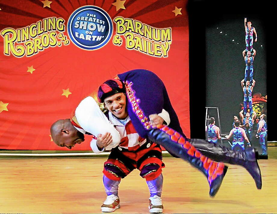 Paulo Dos Santos squats and lifts Ringling Bros. Barnum and Bailey Ringmaster Johnathan Lee Iverson, during a presentation at John C. Daniels School in New Haven Wednesday. The two were at the school to discuss personal achievement and dealing with problems such as bullying. Photo: Melanie Stengel — New Haven Register