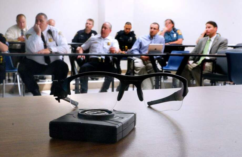 "New Haven-- Local police officials listen to a presentation by Taser, showing their Axon Flex personal camera system for law enforcement. Shown in the foreground is the battery/drive pack and the glasses that holds the camera lens. This allows the video recording to show the same view as the officer wearing the device. Representatives from the company were at the New Haven police department showing off the system.   Photo-Peter Casolino/Register <a href=""mailto:pcasolino@newhavenregister.com"">pcasolino@newhavenregister.com</a>"