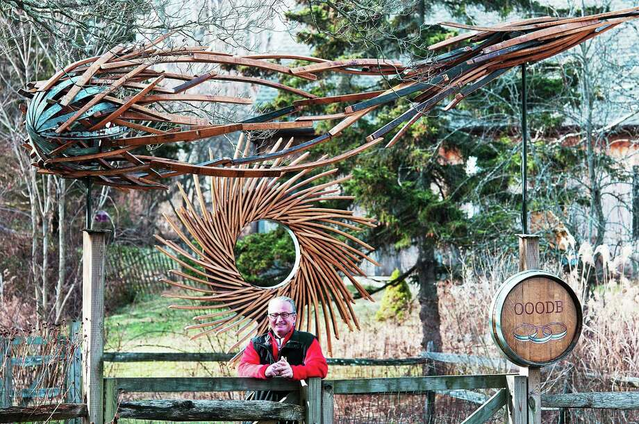 "(Peter Casolino ó New Haven Register)   Doug Ball, a Madison artist creates artwork out of old wine barrels. Behind him are two of his works; ""Meteor,"" top, and ""Hurricane.""  pcasolino@NewHavenRegister Photo: Journal Register Co."