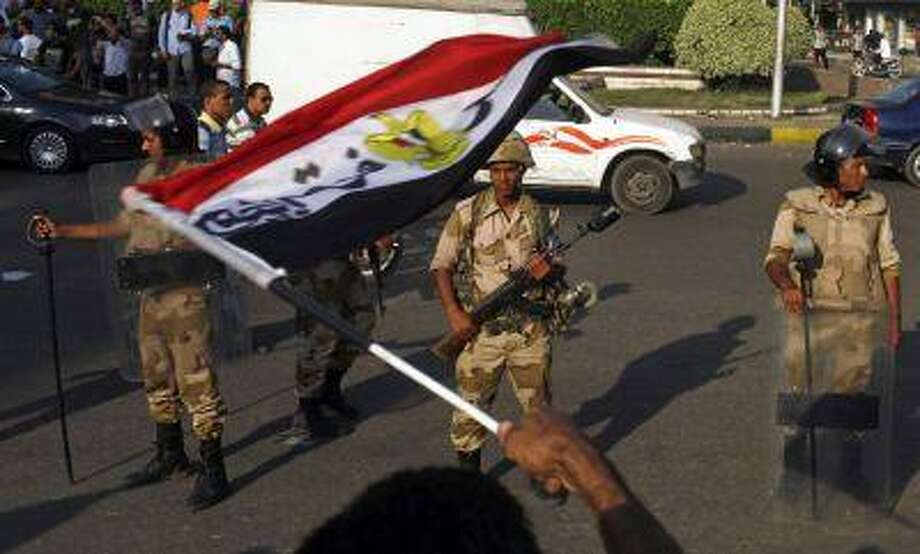 A supporter of overthrown President Mohamed Mursi and the Muslim Brotherhood waves an Egyptian flag near army soldiers standing guard around Cairo University and Nahdet Misr Squar in Giza, on the outskirts of Cairo July 4, 2013. Photo: REUTERS / X02458