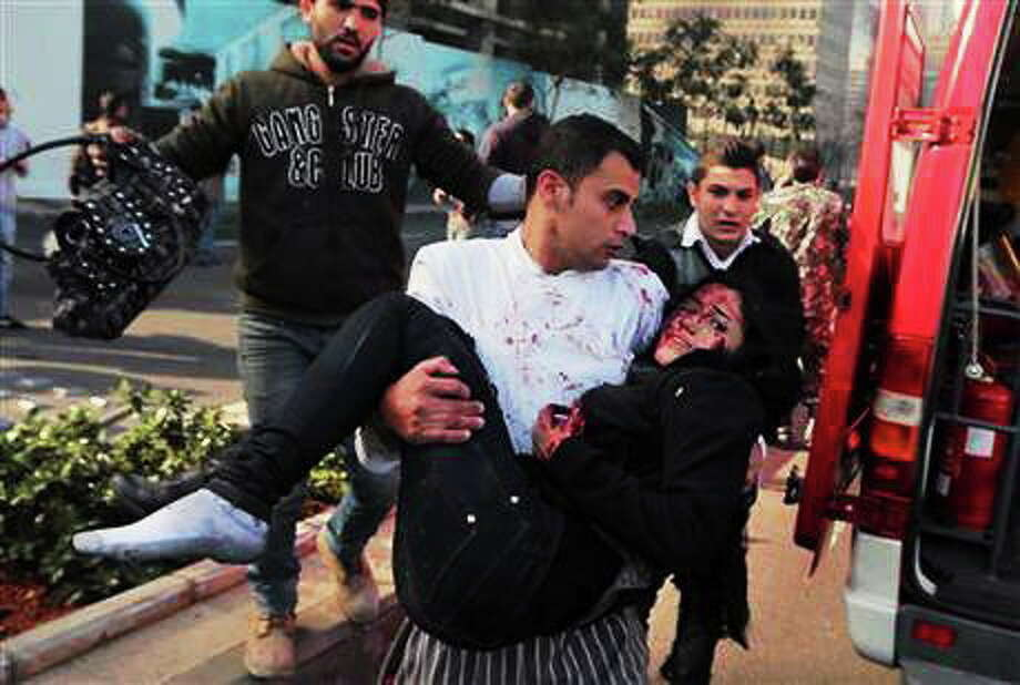 A Lebanese man carries an injured woman at the scene of an explosion in Beirut, Lebanon, Friday, Dec. 27, 2013. A strong explosion has shaken the Lebanese capital, sending black smoke billowing from the center of Beirut. The blast went off a few hundred meters (yards) from the government headquarters and parliament building. (AP Photo/Bilal Hussein) Photo: Journal Register Co.