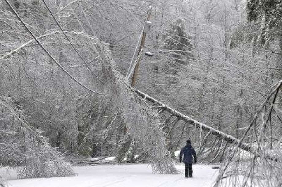 Karen Gibbs walks through a labyrinth of icy broken trees and downed power lines to her home in Belgrade, Maine on Thursday, Dec. 26, 2013.