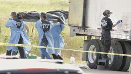 A state police crime lab investigator dusts the exterior of the tractor trailer where dead bodies were found near Victoria, Texas Wednesday, May 14, 2003, while volunteers unload a body from inside the trailer. Seventeen people were found dead Wednesday when authorities opened up a sweltering, airless trailer that had been abandoned at a South Texas truck stop with more than 100 illegal immigrants locked inside. An 18th victim died later at a hospital in one of the deadliest smuggling attempts on record in the United States. (AP Photo/Bryan-College Station Eagle, Butch Ireland)