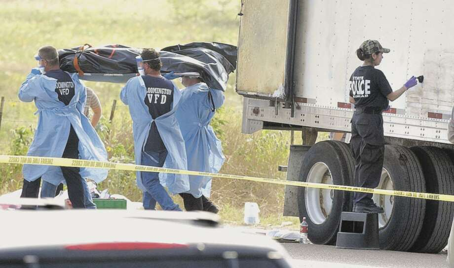 Volunteers remove a body from a tractor-trailer found near Victoria in May 2003 as a crime lab investigator dusts the trailer's exterior. Seventeen bodies were discovered among the more than 100 immigrants locked inside the sweltering, airless trailer. Photo: Associated Press Photos / BRYAN EAGLE