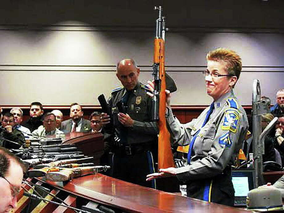 State Police Detective Barbara Mattson holds up a gun for lawmakers at a public hearing in January. Photo: Journal Register Co.