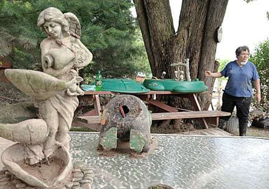 Sally Hall cleans up her Pearl Street backyard. The angel statue remained on the table, in this exact place, while everything around it was thrown into chaos during the flood. (Dispatch Photo by Jolene Cleaver)