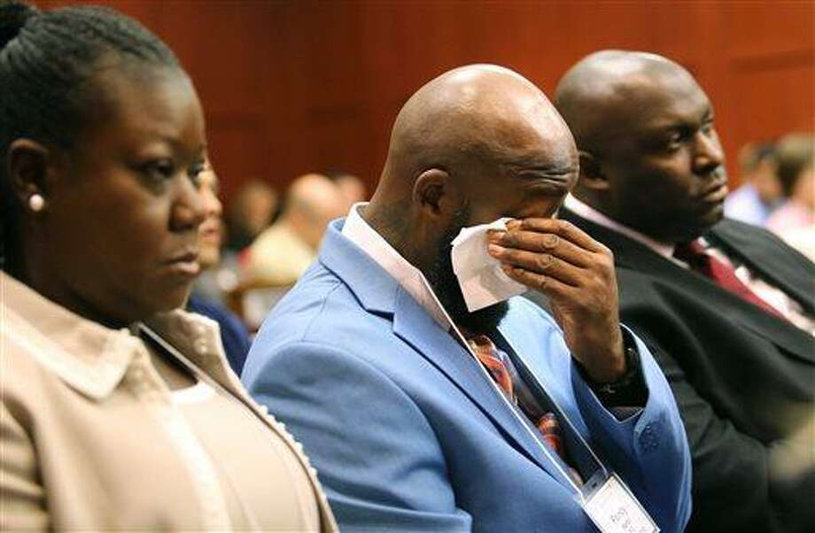 The father of Trayvon Martin, Tracy Martin, cries as he listens to the description of his son's death during opening statements in the George Zimmerman trial, with Sybrina Fulton, Trayvon's mother, left, and Daryl Parks, a family attorney, right, in Seminole circuit court, in Sanford, Fla., Monday, June 24, 2013.  Zimmerman has been charged with second-degree murder for the 2012 shooting death of Trayvon Martin. (AP Photo/Orlando Sentinel, Joe Burbank/Pool) Photo: AP / Pool Orlando Sentinel