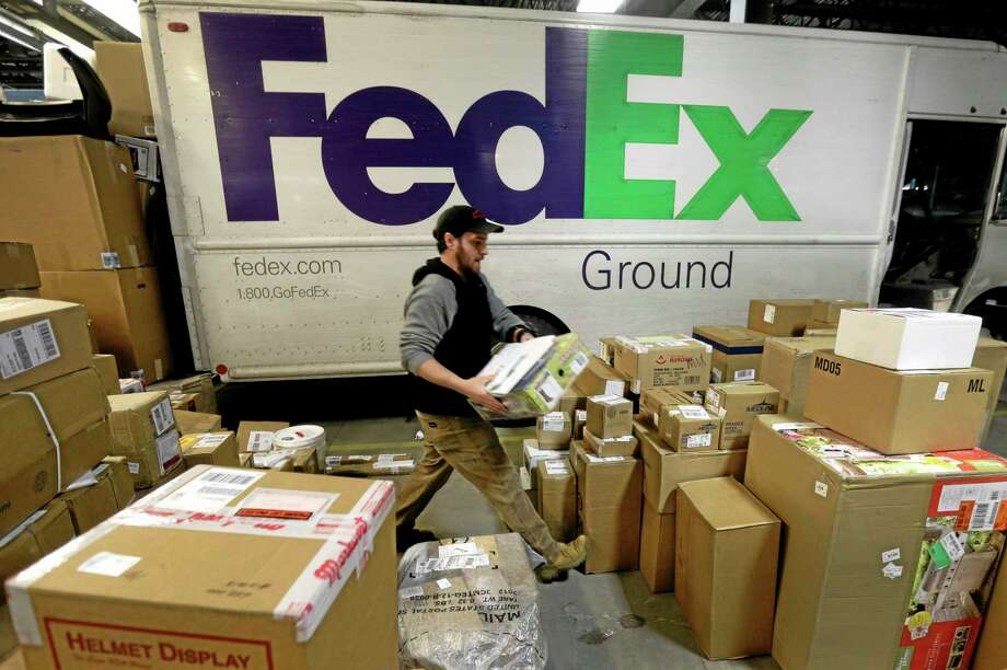 FILE - In this Dec. 16, 2013 file photo, package handler Chris Addison arranges packages before loading a delivery truck at a FedEx sorting facility in Kansas City, Mo. Santa's sleigh didn't make it in time for Christmas for some this year due to shipping problems at UPS and FedEx.The delays were blamed on poor weather earlier this week in parts of the country as well as overloaded systems.  (AP Photo/Charlie Riedel) Photo: AP / AP
