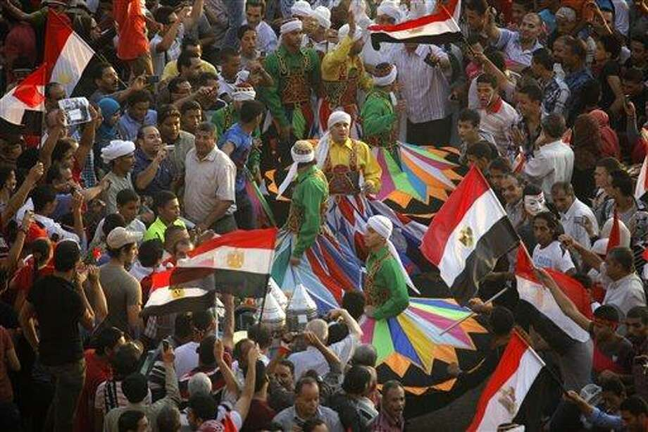 """Egyptian traditional dancers known as whirling dervishes dance as they are surrounded by opponents of Egypt's ousted president Mohammed Morsi in Tahrir Square in Cairo, Egypt, Friday, July 5, 2013. The top leader of Egypt's Muslim Brotherhood has vowed to restore ousted President Mohammed Morsi to office, saying Egyptians will not accept """"military rule"""" for another day. General Guide Mohammed Badie, a revered figure among the Brotherhood's followers, spoke Friday before a crowd of tens of thousands of Morsi supporters in Cairo. A military helicopter circled low overhead.(AP Photo/Amr Nabil) Photo: AP / AP"""