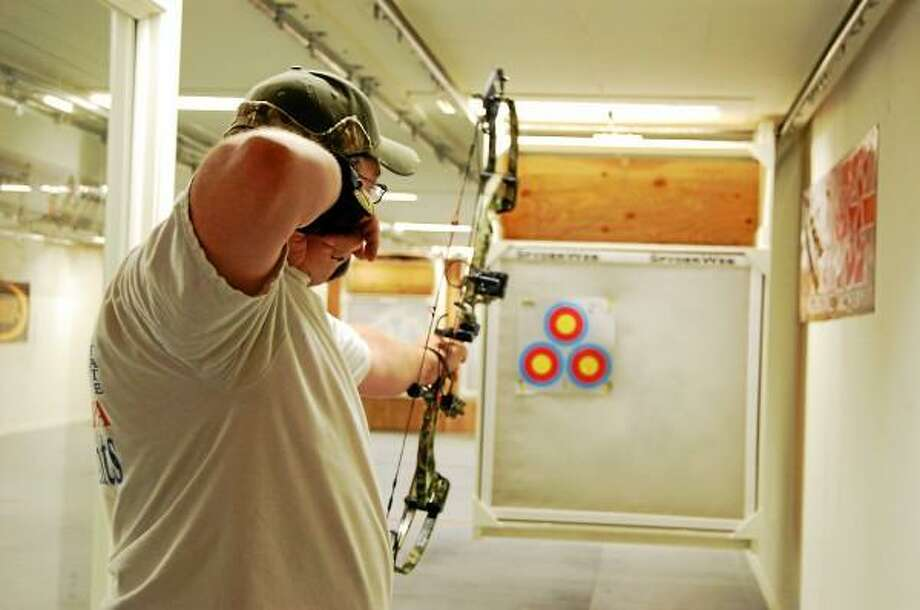 Scott Murray, range manager, aims at a target inside the archery range at Northwest Sporting Goods and Supply in Winsted. (Mercy Quaye--Register Citizen)