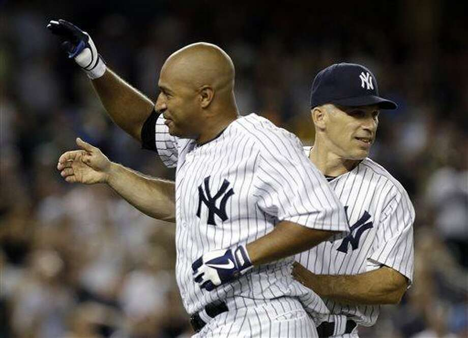 New York Yankees manager Joe Girardi, right, congratulates Vernon Wells after a baseball game against the Baltimore Orioles, Friday, July 5, 2013, in New York. The Yankees won the game 3-2 with Wells' RBI-single. (AP Photo/Frank Franklin II) Photo: AP / AP