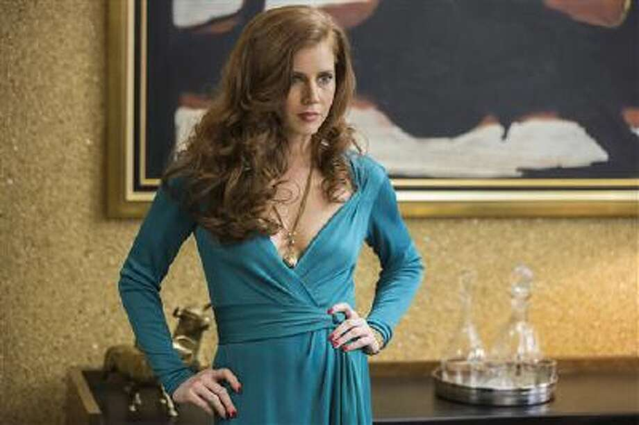 """This film image released by Sony Pictures shows Amy Adams as Sydney Prosser in Columbia Pictures' """"American Hustle."""" Adams' dress is vintage Bob Mackie. She wears vintage jewelry. ?They had ideas, they lived large and they took risks,? costume designer Michael Wilkinson said of the ?70s style that inspired his work in the film. ?Clothes were less structured, had less underpinnings--it was like people didn?t give a damn.? Photo: AP / Sony Pictures"""
