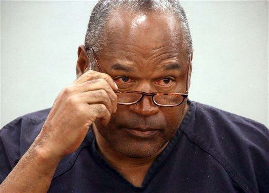 O.J. Simpson removes his glasses as he testifies during an evidentiary hearing in Clark County District Court, Wednesday, May 15, 2013 in Las Vegas. Simpson, who is currently serving a nine to 33-year sentence in state prison as a result of his October 2008 conviction for armed robbery and kidnapping charges, is using a writ of habeas corpus, to seek a new trial, claiming he had such bad representation that his conviction should be reversed. (AP Photo/Las Vegas Review-Journal, Jeff Scheid, Pool) Photo: AP / POOL, Las Vegas Review-Journal