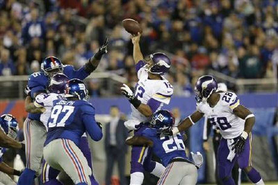Minnesota Vikings quarterback Josh Freeman (12) throws a pass as he is hit by New York Giants' Antrel Rolle (26) during the second half of an NFL football game Monday, Oct. 21, 2013 in East Rutherford, N.J. (AP Photo/Julio Cortez) Photo: AP / AP