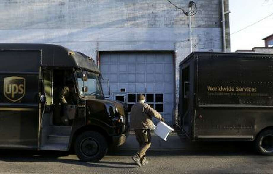 A UPS delivery worker unloads packages from a truck on Dec. 26, 2013, in Newark, N.J.