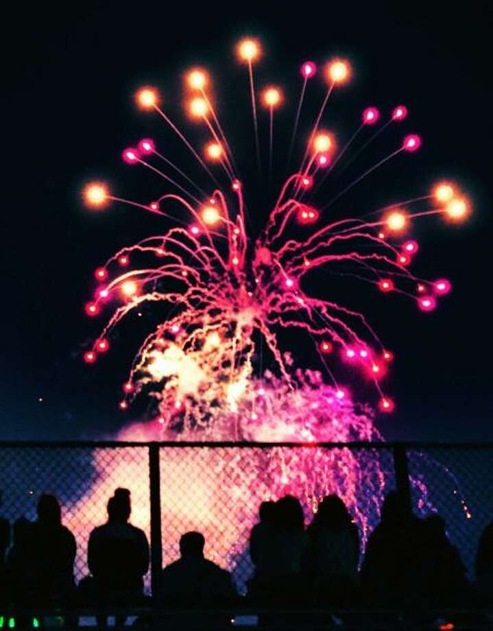 People watch the New Haven fireworks from the bleachers at the Wilbur Cross football field. Melanie Stengel / Register