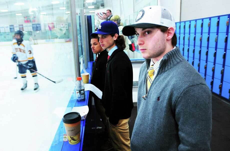 Anthony Iovene, right, watches his Notre Dame-West Haven teammates on the ice during a recent game in Simsbury. Photo: Arnold Gold — Register