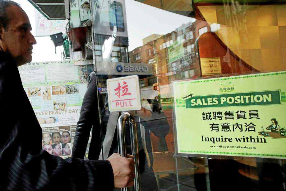 """A customer enters a Chinese bakery in New York that has a sign posted in the door, """"Hiring! Sales Position Inquire within,"""" on Tuesday. The U.S. economy added just 148,000 jobs in September. Photo: Mark Lennihan — The Associated Press   / AP"""