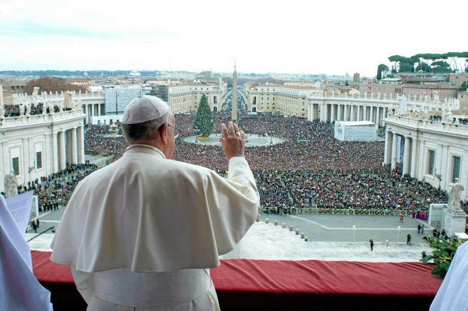 "In this picture provided by the Vatican newspaper L'Osservatore Romano, Pope Francis delivers his ""Urbi et Orbi"" (to the City and to the World) message from the central balcony of St. Peter's Basilica at the Vatican, Wednesday, Dec. 25, 2013. Pope Francis on Christmas day is wishing for a better world, with peace for the land of Jesus' birth, for Syria and Africa as well as for the dignity of migrants and refugees fleeing misery and conflict. Francis spoke from the central balcony of St. Peter's Basilica Wednesday to tens of thousands of tourists, pilgrims and Romans in the square below. He said he was joining in the song of Christmas angels with all those hoping ""for a better world,"" and with those who ""care for others, humbly."" (AP Photo/L'Osservatore Romano, ho) Photo: AP / L'Osservatore Romano"