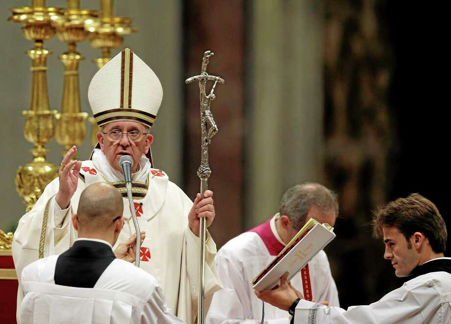 Pope Francis delivers a blessing at the end of the Christmas Eve Mass in St. Peter's Basilica at the Vatican, Tuesday, Dec. 24, 2013. (AP Photo/Gregorio Borgia) Photo: AP / AP