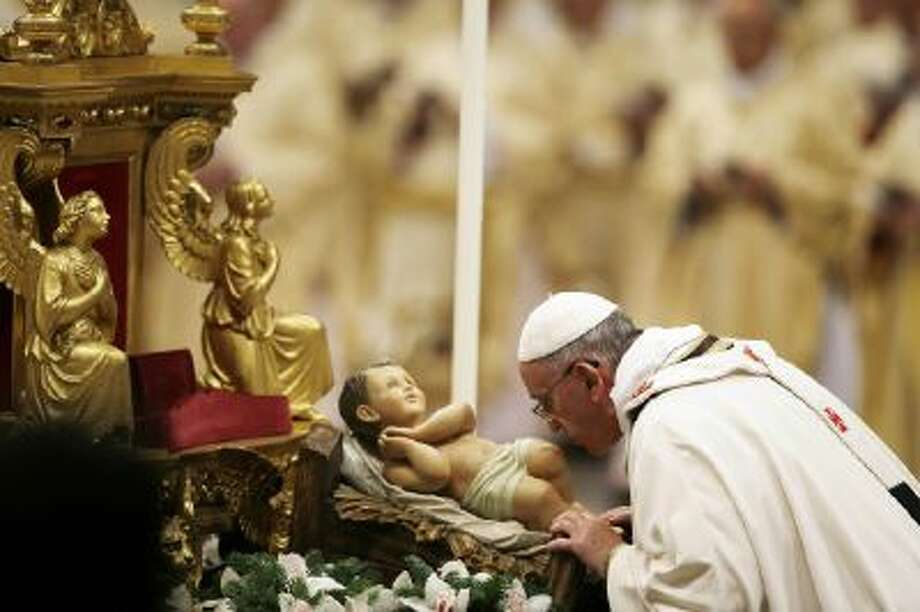 Pope Francis kisses a statue of baby Jesus as he celebrates the Christmas Eve Mass in St. Peter's Basilica at the Vatican, Tuesday, Dec. 24, 2013.