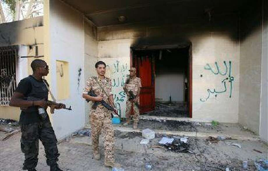 In this Friday, Sept. 14 file photo, Libyan military guards check one of the U.S. Consulate's burnt out buildings during a visit by Libyan President Mohammed el-Megarif, not shown, to the U.S. consulate in Benghazi, Libya. Photo: AP / AP