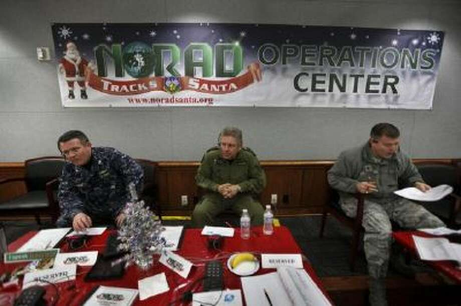 In this 2012 photo, NORAD Deputy Commander Lt. General Alain Parent, center, of the Royal Canadian Air Force, takes phone calls from children asking where Santa is and when he will deliver presents to their house, during the annual NORAD Tracks Santa Operation, at the North American Aerospace Defense Command, or NORAD, at Peterson Air Force Base, in Colorado Springs.