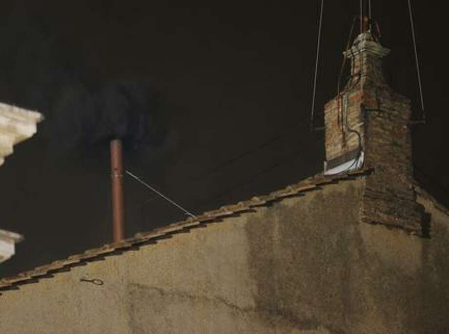 Black smoke emerges from the chimney on the roof of the Sistine Chapel, in St. Peter's Square at the Vatican, Tuesday, March 12, 2013. The black smoke indicates that the cardinals did not elect a new pope. (AP Photo/Dmitry Lovetsky) Photo: AP / AP
