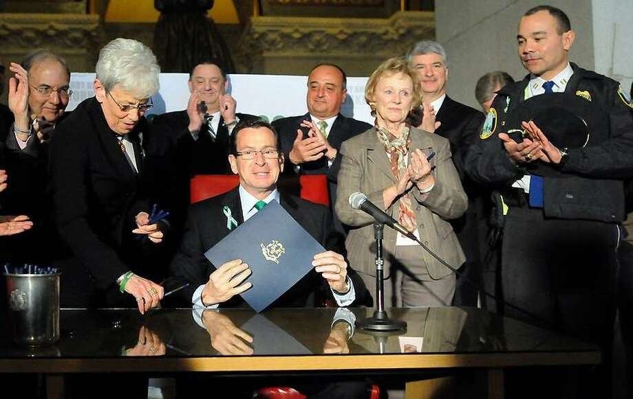 Governor Dannel P. Malloy of Connecticut holds a bill signing ceremony for bi-partisan legislation establishing the Sandy Hook Workers Fund Tuesday March 12, 2013 at the State Capitol in Hartford. The bill signing ceremony commemorates the passage of H.B. 6599 that creates a special fund to assist individuals who suffered psychological trauma as a result of their work related to the Sandy Hook tragedy.  Photo by Peter Hvizdak / New Haven Register Photo: New Haven Register / ©Peter Hvizdak /  New Haven Register