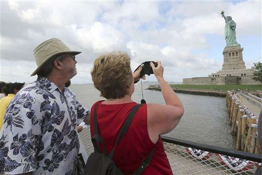 Rodney and Judy Long, of Charlotte, N.C., take a photo of the Statue of Liberty as they arrive on the first tourist ferry to leave Manhattan, Thursday, July 4, 2013, in New York. The Statue of Liberty finally reopened on the Fourth of July months after Superstorm Sandy swamped its island in New York Harbor as Americans across the country marked the holiday with fireworks and barbecues. (AP Photo/Mary Altaffer) Photo: AP / AP
