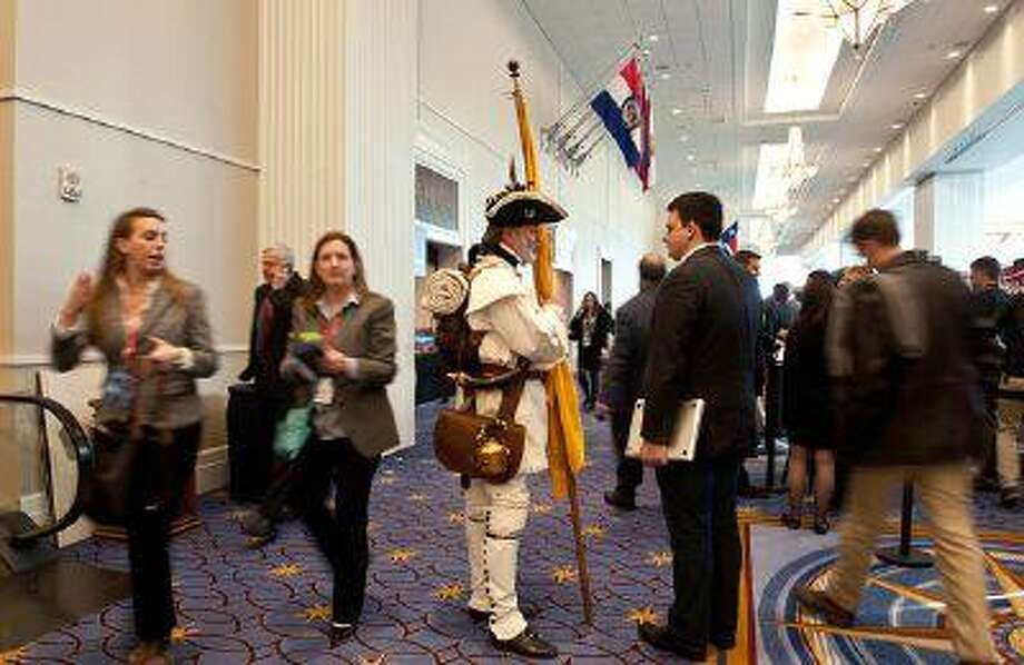 A Tea Party activist dressed in Revolution-era garb speaks with an attendee at the Conservative Political Action Conference (CPAC) in National Harbor, Maryland, on March 15, 2013. (Nicholas Kamm/AFP via Getty Images)