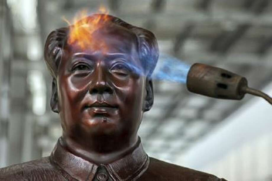 A worker use a torch to process a statue of Mao Zedong at a factory specializing in making busts and sculptures of the late leader in Shaoshan, China, on Dec. 5.