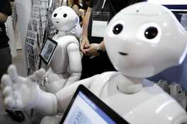 SoftBank Group Corp.'s Pepper humanoid robots stand at a booth at SoftBank World 2017 in Tokyo, Japan, on Thursday, July 20, 2017. SoftBank World, the company's annual two-day event for customers and suppliers, runs through July 21. Photographer: Kiyoshi Ota/Bloomberg