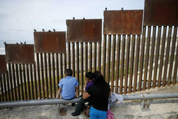 "FILE - In this March 2, 2016 file photo, a family looks towards metal bars marking the U.S. border where it meets the Pacific Ocean, in Tijuana, Mexico. Candidate Donald Trump's promise to build a ""big, beautiful wall"" on the Mexican border conjured images of an inpenetrable structure spanning 2,000 miles. Trump still insists he'll build the wall, but his top aides have made clear it won't be ""from sea to shining sea.""  (AP Photo/Gregory Bull, File)"
