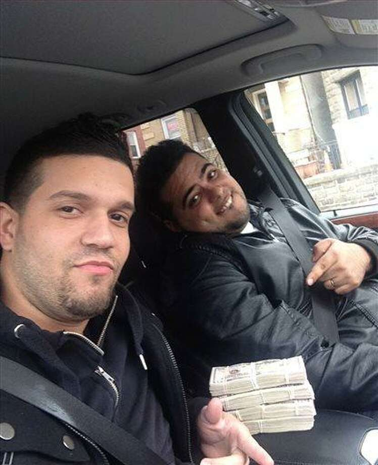 In this undated photo provided by the United States Attorney's Office for the Southern District of New York, Elvis Rafael Rodriguez, left, and Emir Yasser Yeje, pose with bundles of cash allegedly stolen using bogus magnetic swipe cards at cash machines throughout New York. Prosecutors in New York on Thursday, May 9, 2013 said that they are members of worldwide gang of criminals who stole $45 million in hours by hacking into a database of prepaid debit cards and draining cash machines around the globe. An indictment unsealed Thursday accused U.S. cell ringleader Alberto Yusi Lajud-Pena and seven other New York suspects of withdrawing $2.8 million in cash from hacked accounts in less than a day.  (AP Photos/U.S. Attorney's Office for the Southern District of New York) Photo: AP / US Attorney's Office