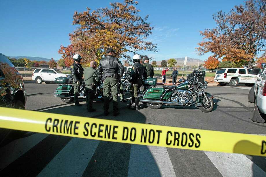 Police secure the scene near Sparks Middle School after a shooting in Sparks, Nev., on Monday, Oct. 21, 2013.  Authorities are reporting that two people were killed and two wounded at the Nevada middle school. (AP Photo/Kevin Clifford) Photo: AP / FR159396 AP