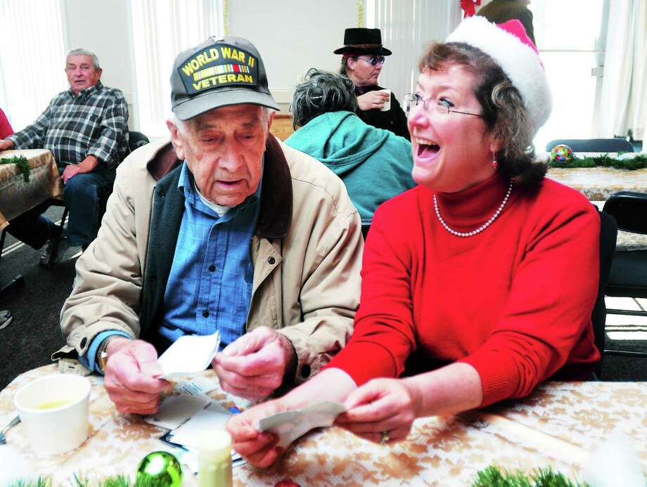 Daniel Howard (left) of Milford show photographs to Susan Bedworth (right) of Milford at a Christmas day dinner at the Milford Elks Lodge No. 1589 on 12/25/2013. Photo: (Arnold Gold - New Haven Register)