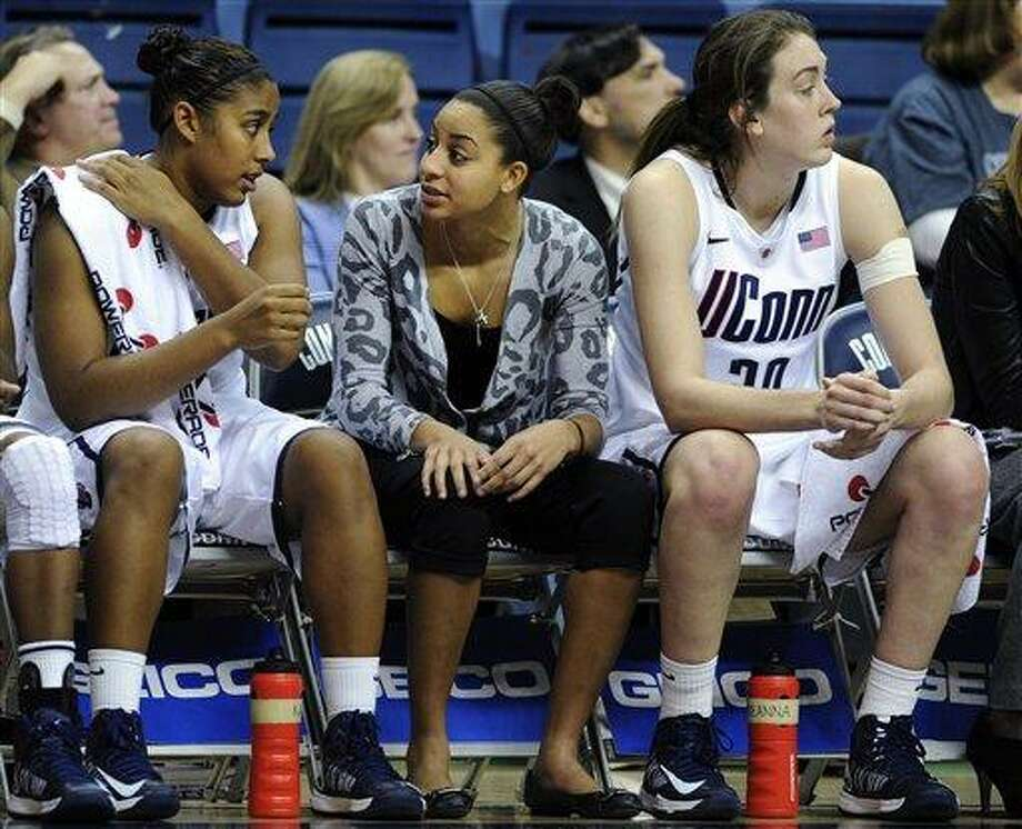 Connecticut's Bria Hartley, center, speaks with Kaleena Mosqueda-Lewis, left, as Breanna Stewart watches play during the second half of Connecticut's 103-39 victory over Charleston in an NCAA college basketball game in Storrs, Conn., Sunday, Nov. 11, 2012. Hartley watched the game in street clothes after being sidelined with an ankle injury. (AP Photo/Fred Beckham) Photo: ASSOCIATED PRESS / AP2012