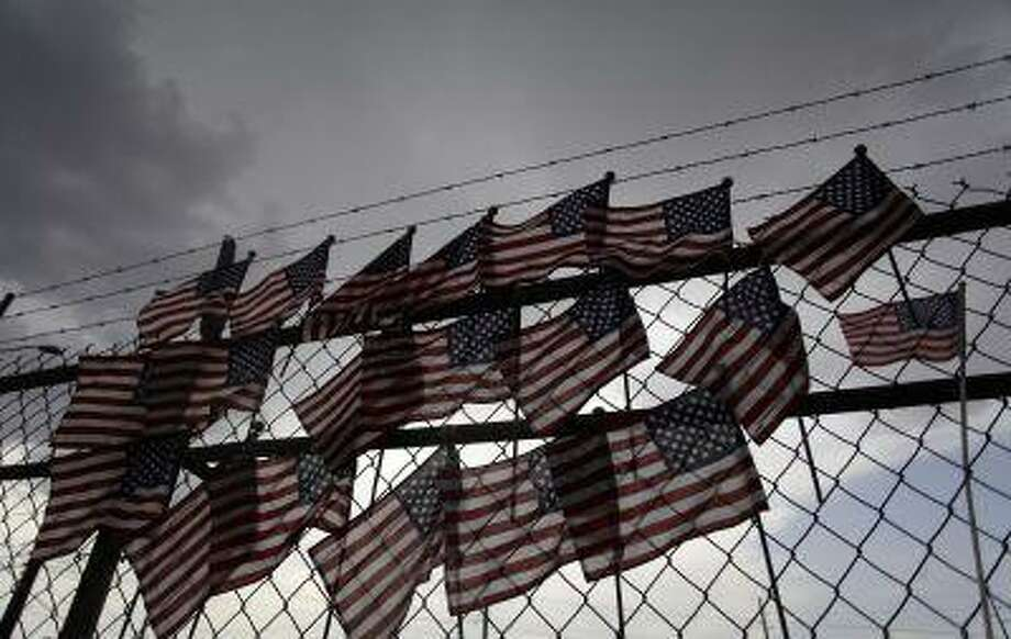 American flags representing the 19 firefighters who perished battling a fast-moving wildfire are displayed on a fence at a makeshift memorial in Prescott, Arizona July 1, 2013. (Joshua Lott/Reuters) Photo: REUTERS / X01971