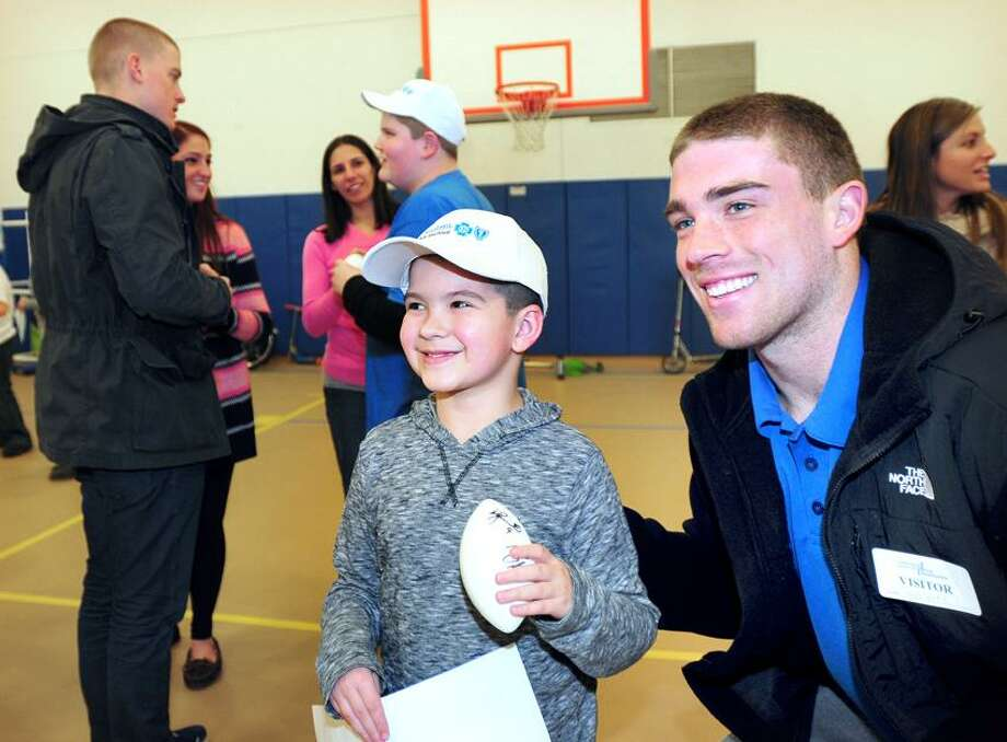 Jack Masters (center), 8, has his photograph taken with Walter Camp All-American Zach Ertz (right) of Stanford at the Connecticut Center for Child Development in Milford on 1/11/2013.Photo by Arnold Gold/New Haven Register   AG0480B