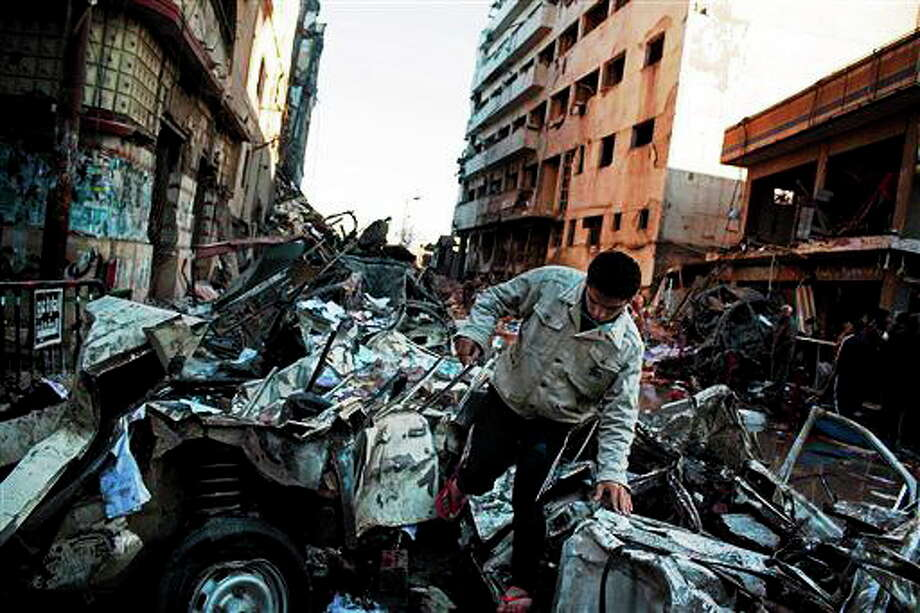 """An Egyptian man makes his way through rubble at the scene of an explosion at a police headquarters building that killed at least a dozen people, wounded more than 100, and left scores buried under the rubble, in the Nile Delta city of Mansoura, 110 kilometers (70 miles) north of Cairo, Egypt, Tuesday, Dec. 24, 2013. The country's interim government accused the Muslim Brotherhood of orchestrating the attack, branding it a """"terrorist organization."""" No one immediately claimed responsibility for the bombing, which came a day after an al-Qaida-inspired group called on police and army personnel to desert or face death at the hands of its fighters. (AP Photo/Ahmed Ashraf) Photo: AP / AP"""
