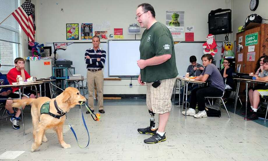 Reese, a three year old golden retriever service dog, carries his leash for Phil Bauer (center) of Dobbs Ferry, New York, during a visit to an eighth grade class at West Shore Middle School in Milford on 5/13/2013.Photo by Arnold Gold/New Haven Register